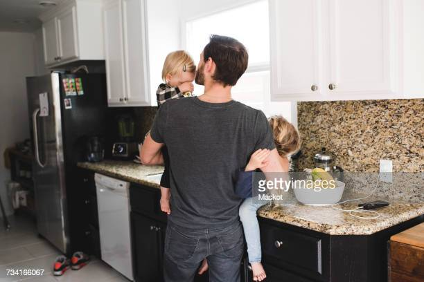 Rear view of father taking care of daughters in kitchen at home