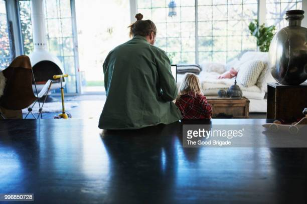 Rear view of father using laptop by daughter sitting on hardwood floor at home