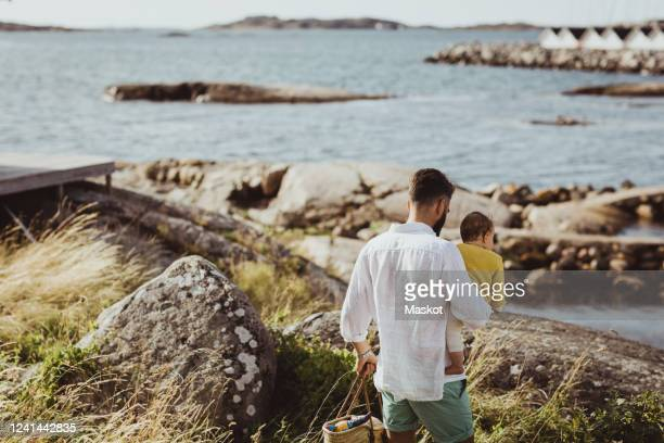 rear view of father with daughter walking on rock formation by sea - paternity leave stock pictures, royalty-free photos & images