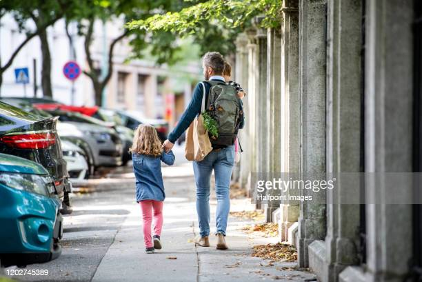 rear view of father with small girls walking outdoors on the sidewalk in city. - human body part stock pictures, royalty-free photos & images
