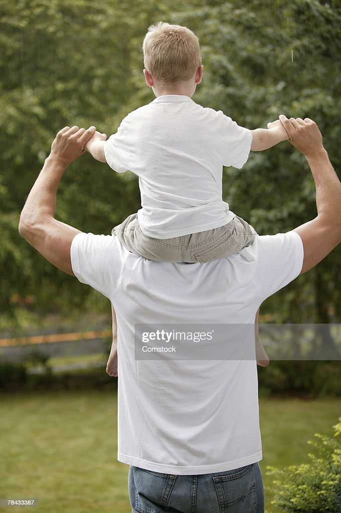 Rear view of father with son riding on his shoulders : Stockfoto