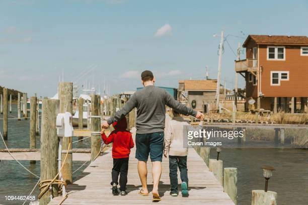 rear view of father with sons walking on pier over sea against sky during sunny day - outer banks stock pictures, royalty-free photos & images