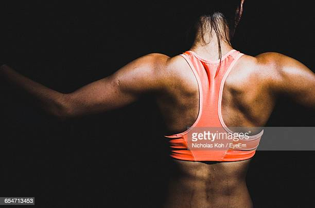 Rear View Of Female Athlete Against Black Background