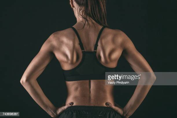 Rear view of female athlete wearing sports bra standing with hands on hip against black background