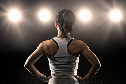 Rear view of female athlete wearing sports bra standing with hands - gettyimageskorea