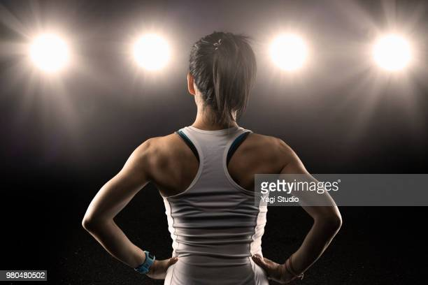 rear view of female athlete wearing sports bra standing with hands - rear view photos stock photos and pictures