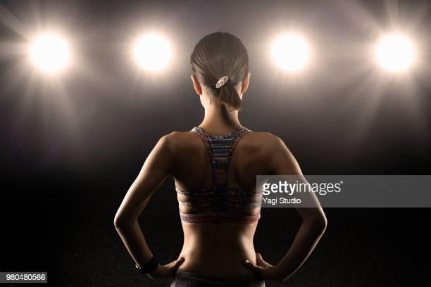 rear view of female athlete wearing sports bra standing with hands - menschlicher rücken stock-fotos und bilder