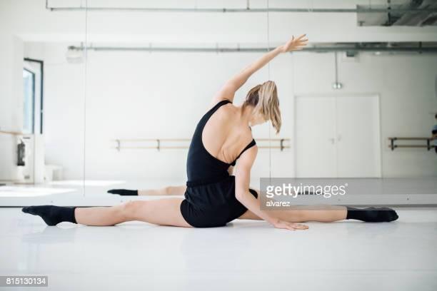 Rear view of female ballet dancer doing the splits