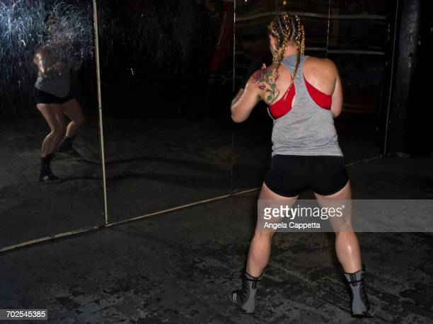 Rear view of female boxer sparring looking in gym wall mirror