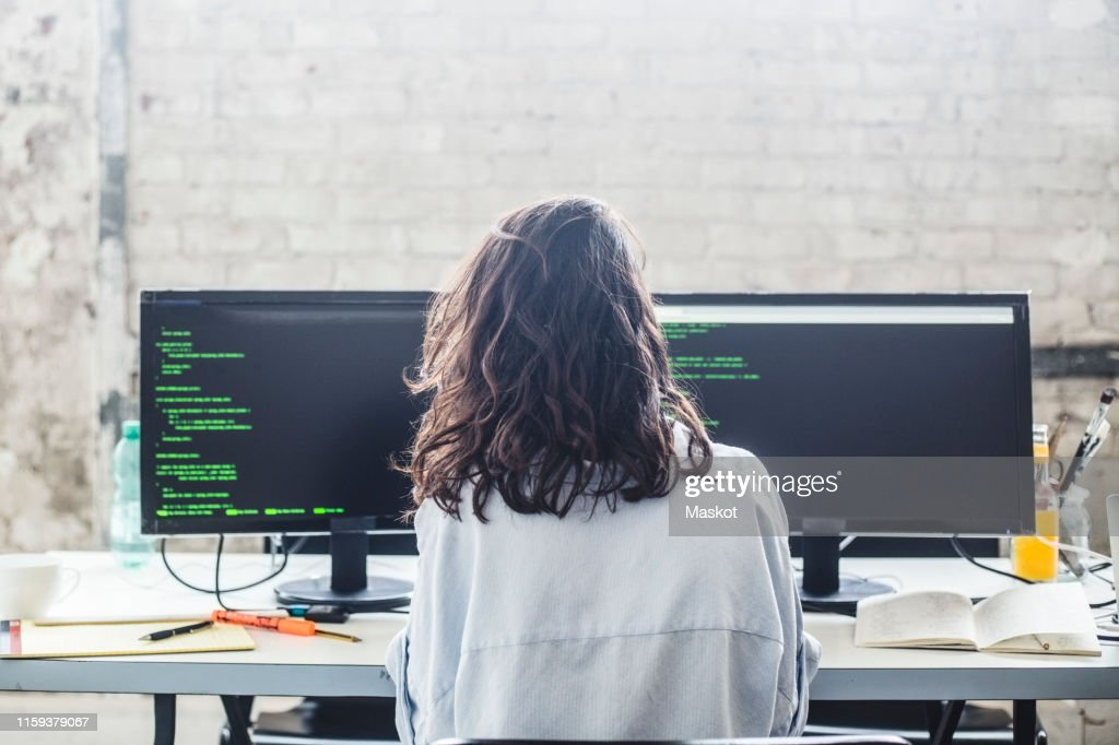 Rear view of female computer hacker coding at desk in creative office : Stock Photo