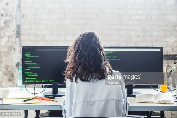 rear view of female computer hacker coding at desk in creative office - coding stock pictures, royalty-free photos & images
