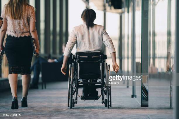 rear view of female entrepreneur walking with disabled businesswoman in corridor at workplace - persons with disabilities stock pictures, royalty-free photos & images