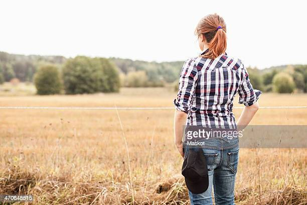 Rear view of female farmer standing at field
