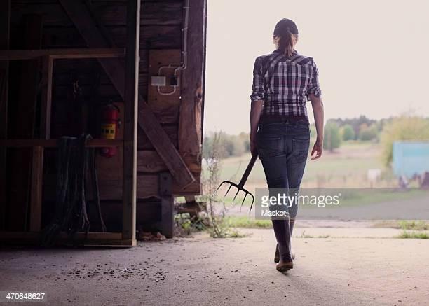 Rear view of female farmer with pitchfork walking in barn