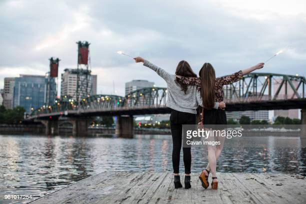 rear view of female friends burning firework while standing against burlington northern railroad bridge 9.6 - portland oregon stock pictures, royalty-free photos & images