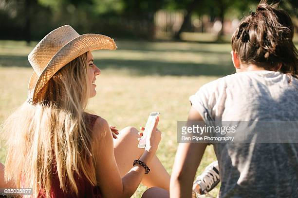 rear view of female friends chatting in park - brixton stock pictures, royalty-free photos & images
