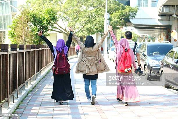 Rear View Of Female Friends Holding Hands With Arms Raised On Walkway