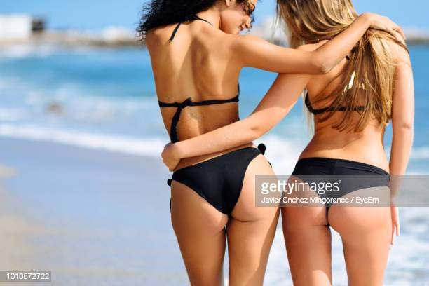 rear view of female friends in bikinis standing at beach - beautiful female bottoms stock pictures, royalty-free photos & images