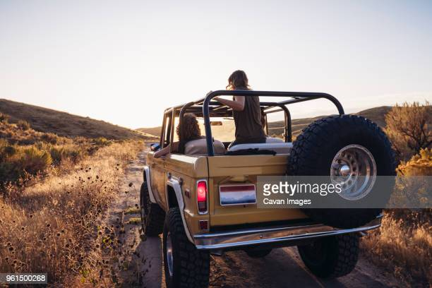 rear view of female friends in off-road vehicle on field against clear sky - jeep stock pictures, royalty-free photos & images