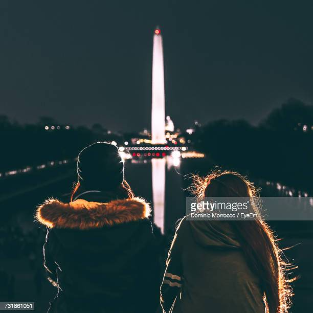 Rear View Of Female Friends Looking At Illuminated Washington Monument At Night