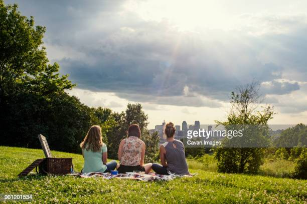 rear view of female friends relaxing at park on sunny day - 隣り合わせ ストックフォトと画像
