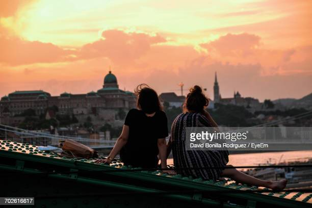 Rear View Of Female Friends Sitting On Liberty Bridge In City Against Orange Sky