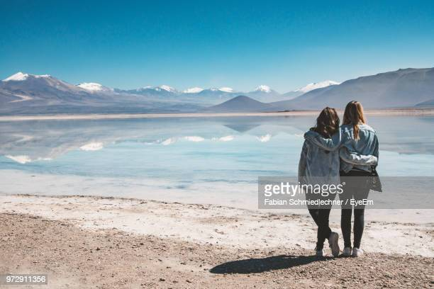 Rear View Of Female Friends Standing By Lake With Reflection