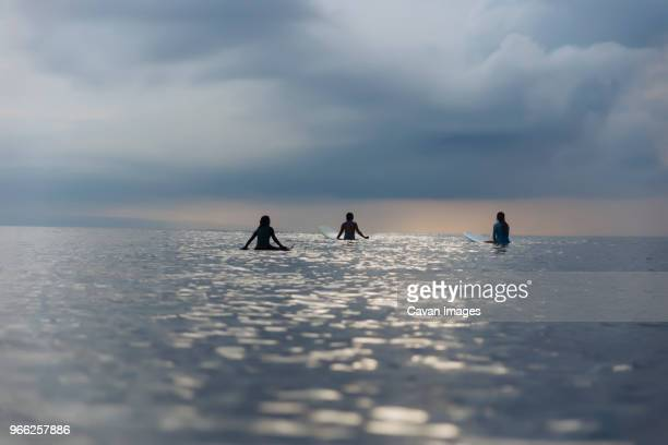 rear view of female friends surfing in sea against cloudy sky - seascape stock pictures, royalty-free photos & images