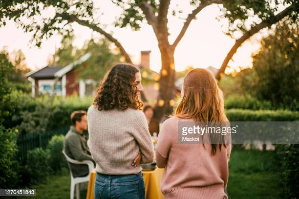 rear view of female friends talking in yard for social gathering - four people stock pictures, royalty-free photos & images