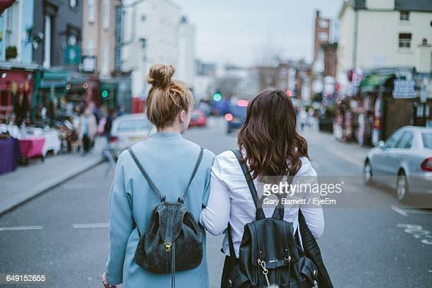 Rear View Of Female Friends Walking On Road In City