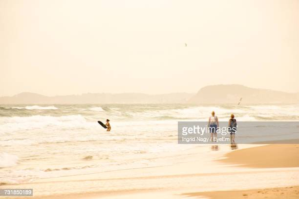 Rear View Of Female Friends Walking On Shore At Beach