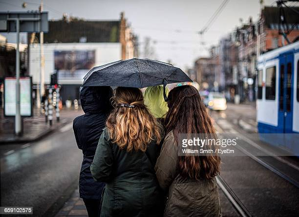 Rear View Of Female Friends With Umbrella Walking On City Street During Monsoon