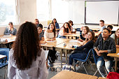 Rear View Of Female High School Teacher Standing At Front Of Class Teaching Lesson