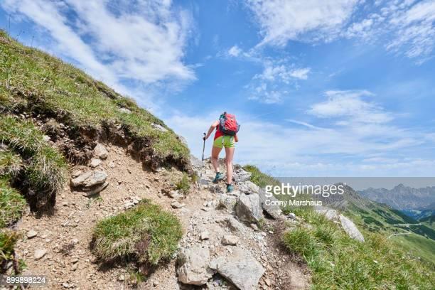 Rear view of female hiker hiking up Tannheim mountains, Tyrol, Austria