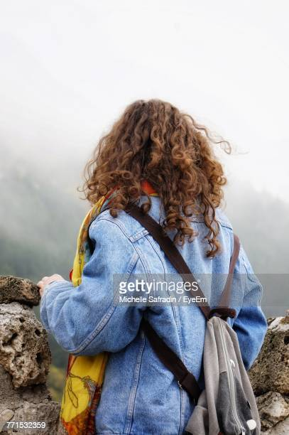 Rear View Of Female Hiker Standing Against Sky During Foggy Weather