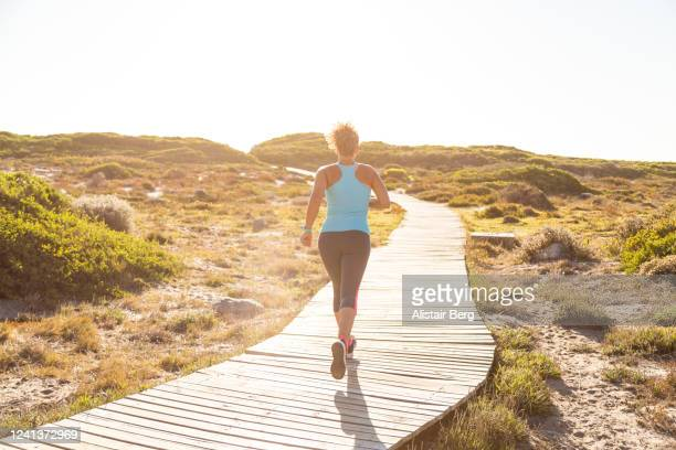 rear view of female jogger on boardwalk - active lifestyle stock pictures, royalty-free photos & images