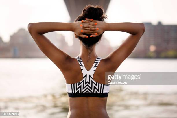 rear view of female jogger with hands behind head - sports bra stock pictures, royalty-free photos & images