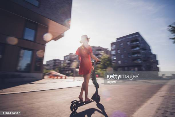 rear view of female on electric scooter. - mobility scooter stock photos and pictures