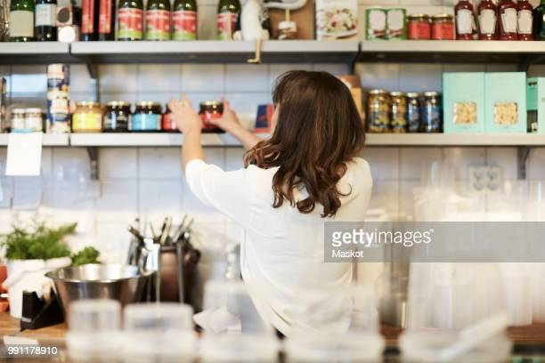 Rear view of female owner arranging food products on shelf in store