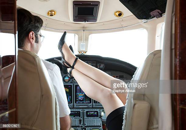 rear view of female pilot with feet up in cockpit of private jet - high heels short skirts stock photos and pictures