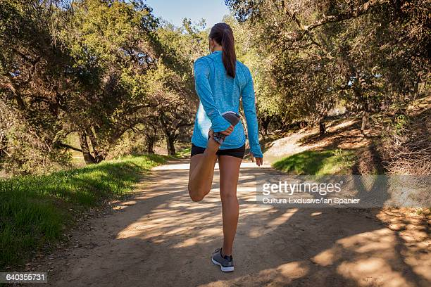 Rear view of female runner stretching leg on woodland track