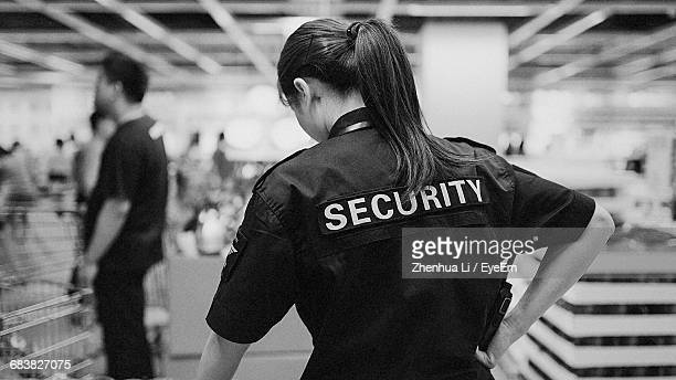 Rear View Of Female Security Guard At Mall