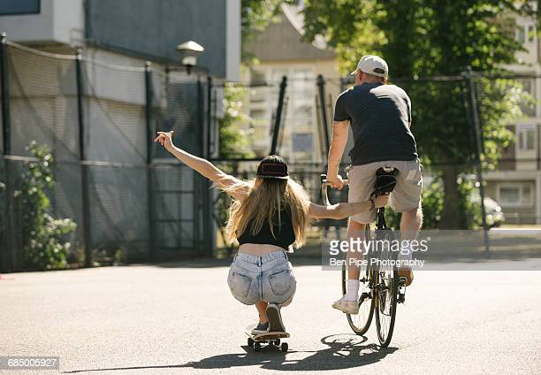 Rear view of female skateboarder and male cyclist on basketball court
