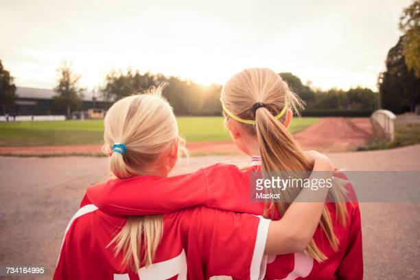 Rear view of female soccer friends standing on footpath looking at field during sunset