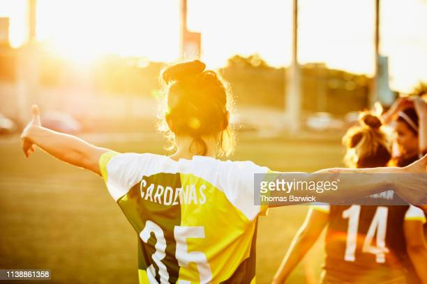 Rear view of female soccer player celebrating on field during soccer game
