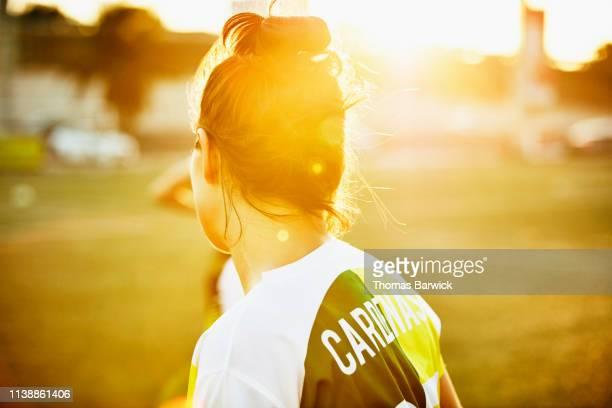 rear view of female soccer player on field during game - frauenfußball stock-fotos und bilder