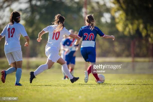 vista trasera de las jugadoras de fútbol femeninos durante un partido en un estadio. - equipo de fútbol fotografías e imágenes de stock