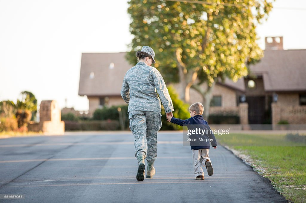 Rear view of female soldier walking with son at military air force base : Stock Photo