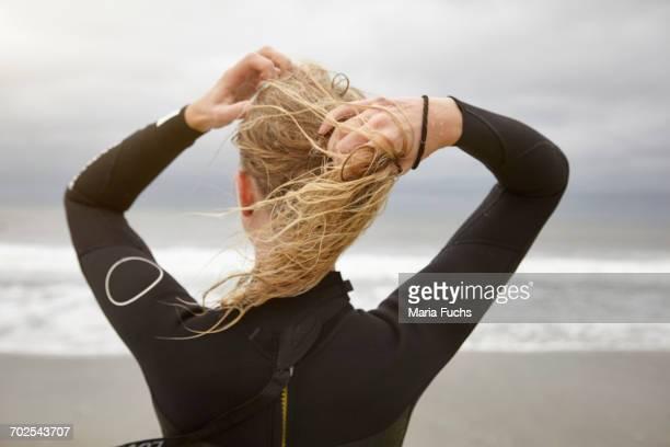 rear view of female surfer tying wet blond hair on rockaway beach, new york, usa - blond frauen strand stock-fotos und bilder