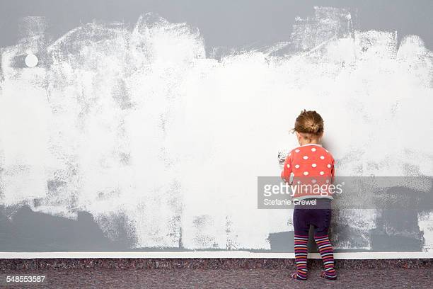 Rear view of female toddler painting wall
